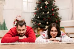Happy couple at christmastime. Beautiful happy young couple lying on carpet and smiling at camera at christmastime stock image