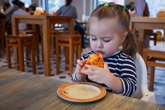 Beautiful happy young girl biting off big slice of fresh made pizza. She sit at white chair in cafe and enjoy yummy meal royalty free stock image