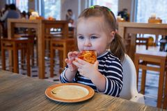 Beautiful happy young girl biting off big slice of fresh made pizza. She sit at white chair in cafe and enjoy yummy meal royalty free stock photos