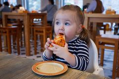 Beautiful happy young girl biting off big slice of fresh made pizza. She sit at white chair in cafe and enjoy yummy meal stock photo