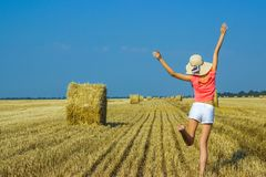 Beautiful happy young girl jumping for joy in the air near a haystack royalty free stock image