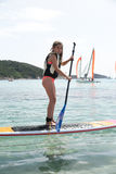 Beautiful and happy young girl learning paddle-surf Royalty Free Stock Photography