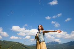 Beautiful happy young girl playing with soap bubbles. At outdoor location Stock Photography