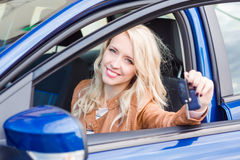 Beautiful happy young girl sitting in the car. Beautiful happy young girl sitting in her car showing carkey Stock Photo