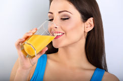 Beautiful happy young healthy casual woman drinking orange juice royalty free stock photo