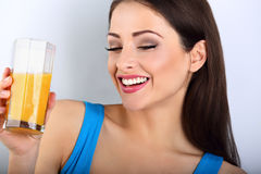 Beautiful happy young healthy casual woman drinking orange juice Stock Image