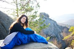 Woman sitting alone in sleeping bag on big mountain rock and smiling royalty free stock photo