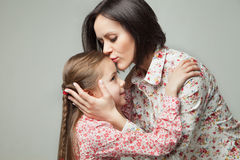 Beautiful and happy young mother kissing her small daughter. Stock Photos