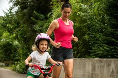 Beautiful and happy young mother teaching her cute daughter to ride a bicycle. Both smiling, Summer street in background stock photos