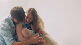 Beautiful happy young parents smile to their precious newborn son mother lulling her baby in a rocking chair. 4k stock video footage