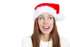 Beautiful happy young santa girl helper in red hat, looking sideways dreaming about gifts Stock Images
