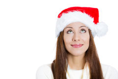 Beautiful happy young santa girl helper in red hat, looking upwards dreaming about gifts Stock Photos