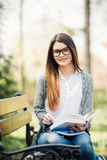 Beautiful and happy young student girl sitting on bench, holding book in her hands, smiling and looking into the camera. Summer or spring green park in Stock Images