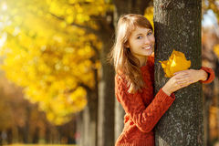 Beautiful happy young woman in the autumn park. Joyful woman is Stock Photo