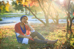 Beautiful happy young woman in the autumn park. Joyful woman is talking on a smart phone outdoors in a bright yellow Stock Image