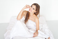 Beautiful happy young woman on bed Stock Image