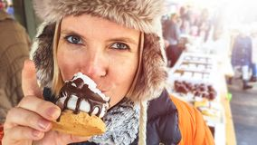 Beautiful happy young woman with big eyes in fluffy winter hat eating outdoor on a sunny day chocolate cake sweets with a white cr stock image