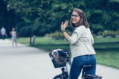 Beautiful happy young woman on bike in park Stock Photo