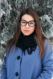 Beautiful happy young woman with black glasses wearing winter coat color Blue Cobalt and black scarf covered with snow. Flakes Royalty Free Stock Photo