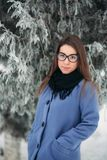 Beautiful happy young woman with black glasses wearing winter coat color Blue Cobalt and black scarf covered with snow. Flakes Royalty Free Stock Images