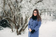 Beautiful happy young woman with black glasses wearing winter coat color Blue Cobalt and black scarf covered with snow. Flakes Stock Photography