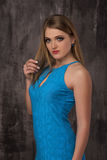 Beautiful happy young woman in blue dress on grey background Stock Image