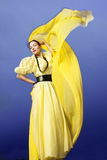 Beautiful and happy young woman dancing. With yellow chiffon dress in a blue sky Stock Photo
