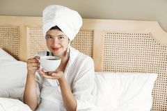 Free Beautiful Happy Young Woman Drinking Coffee Or Tea In Bed In Hotel Room Or Home Bedroom. Fashionable  Brunette Girl In White Towel Royalty Free Stock Photography - 148653387
