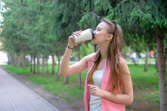 Beautiful happy young woman drinking coffee in park Royalty Free Stock Photography