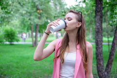 Beautiful happy young woman drinking coffee in park Stock Image