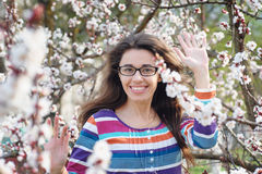 Beautiful happy young woman enjoying smell in a flowering spring garden Stock Image
