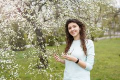 Beautiful happy young woman enjoying smell in a flowering spring garden royalty free stock photos