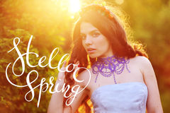 Beautiful happy young woman enjoying smell in a flowering spring garden with letters Hello sprint Stock Images