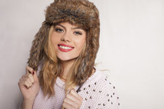 Beautiful happy young woman in a furry winter hat Royalty Free Stock Photos