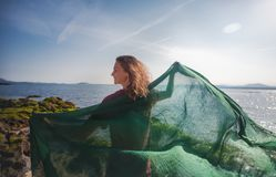 Beautiful happy young woman with green scarf on the seashore on a sunny spring day royalty free stock photos