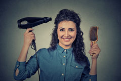 Beautiful happy young woman with the hair dryer and brush. Closeup portrait beautiful happy young woman with the hair dryer and brush isolated on gray wall royalty free stock image