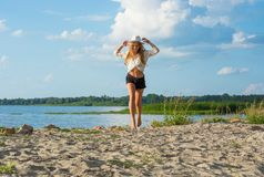 Beautiful happy young woman in a hat and in shorts running along royalty free stock photography