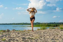 Beautiful happy young woman in a hat and in shorts running along royalty free stock image