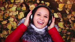 Beautiful happy young woman with headphones lying on autumn leaves listening to music. 1920x1080. Young caucasian brunette woman listening music in headphones in stock footage