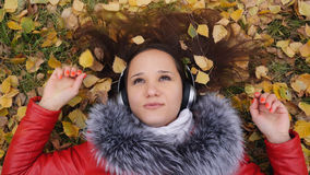 Beautiful happy young woman with headphones lying on autumn leaves listening to music. Season, technology and people Royalty Free Stock Photography