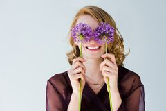 Beautiful happy young woman holding bright purple flowers. Isolated on grey royalty free stock photography
