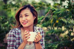 Beautiful happy young woman holding a cup of coffee in park. royalty free stock photography