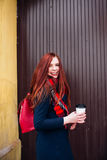 Beautiful happy young woman holding a paper cup and drinking coffee. Cheerful woman with red long hair in the street stock image
