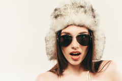 Beautiful and happy young woman isolated on white and wearing a fur hat and sunglasses Stock Image