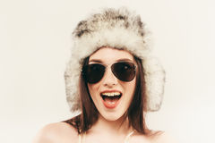 Beautiful and happy young woman isolated on white and wearing a fur hat and sunglasses Stock Photo
