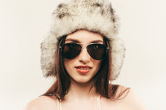 Beautiful and happy young woman isolated on white and wearing a fur hat and sunglasses Royalty Free Stock Photos