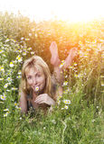 Beautiful happy young woman lies in the field of camomiles Royalty Free Stock Photos
