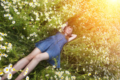 Beautiful happy young woman lies in the field of camomiles Stock Images