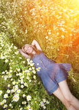 Beautiful happy young woman lies in the field of camomiles Royalty Free Stock Image