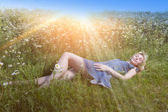 The beautiful happy young woman lies in the field of camomiles Royalty Free Stock Photography